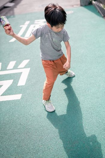 High angle view of boy playing on road in city