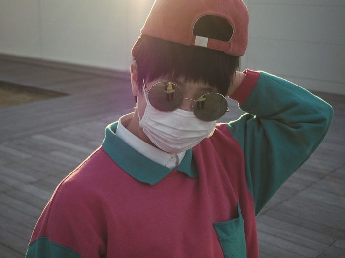 High angle view of woman wearing sunglasses and cap during sunset