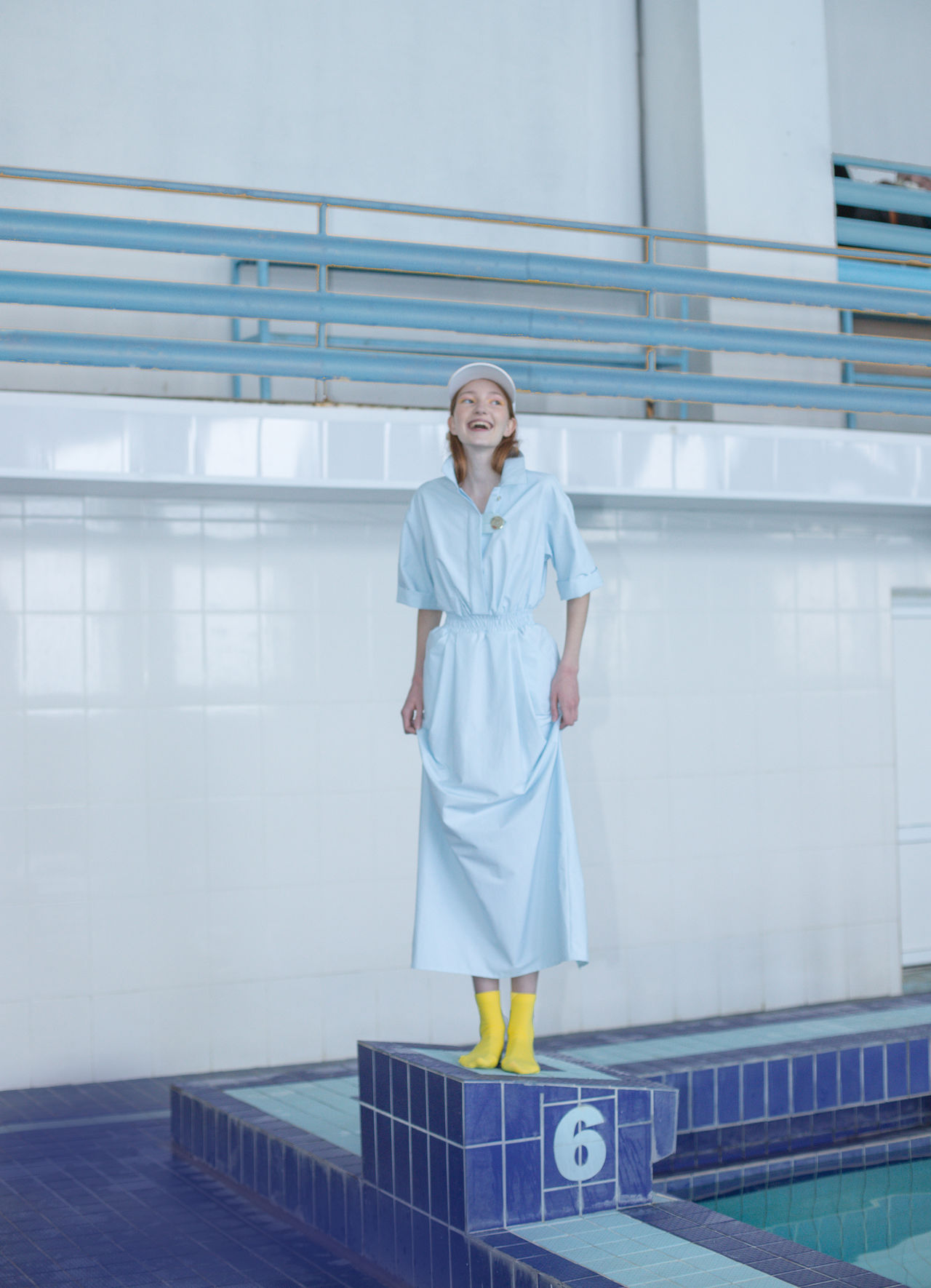 Smiling teenage girl looking away while standing at poolside against wall