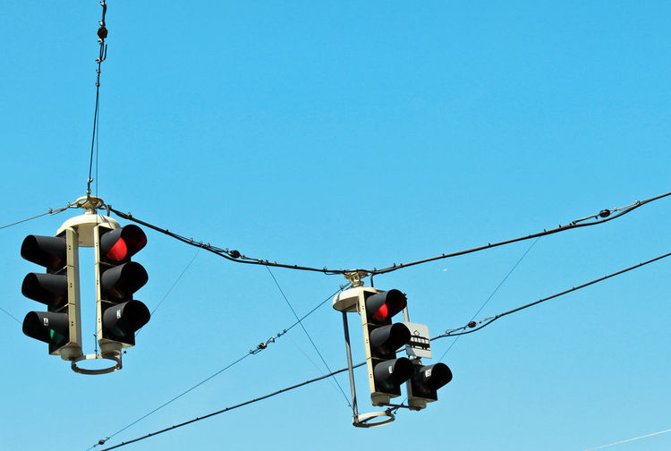 Low angle view of road signals against clear blue sky
