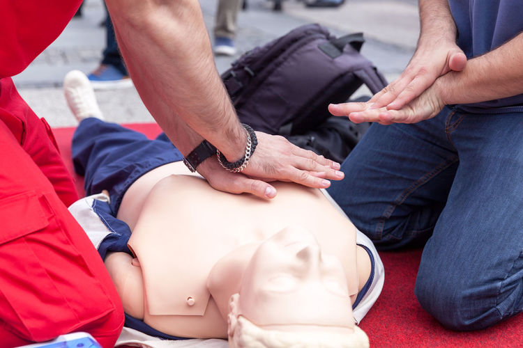 Instructor teaching cpr on dummy