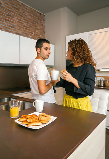 Couple Having Breakfast While Standing In Kitchen
