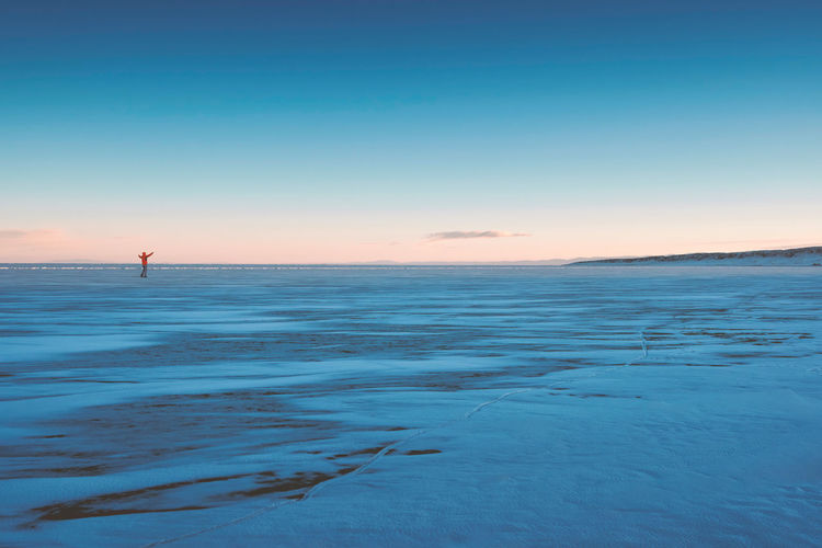 Distant view man with arms raised standing on frozen lake during sunset