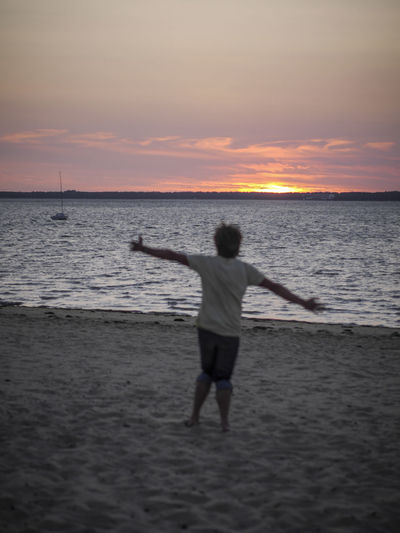 Rear view of silhouette man standing at beach during sunset