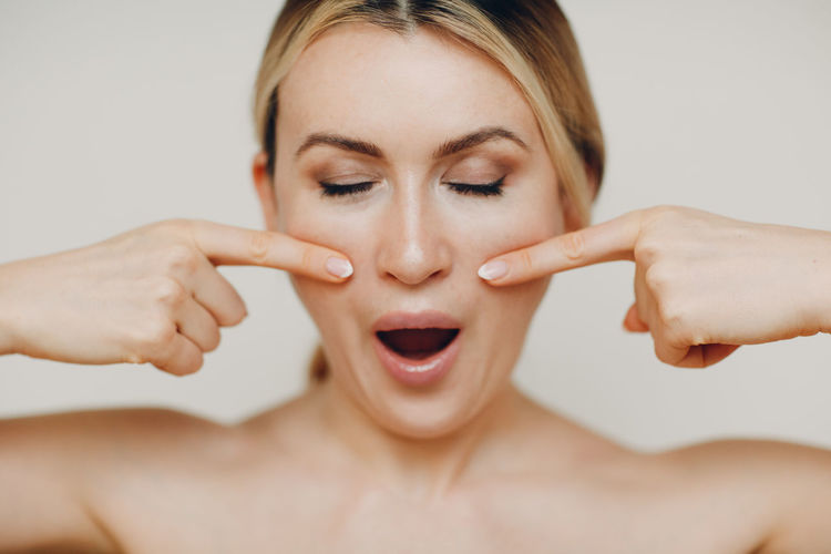 Woman making face against beige background