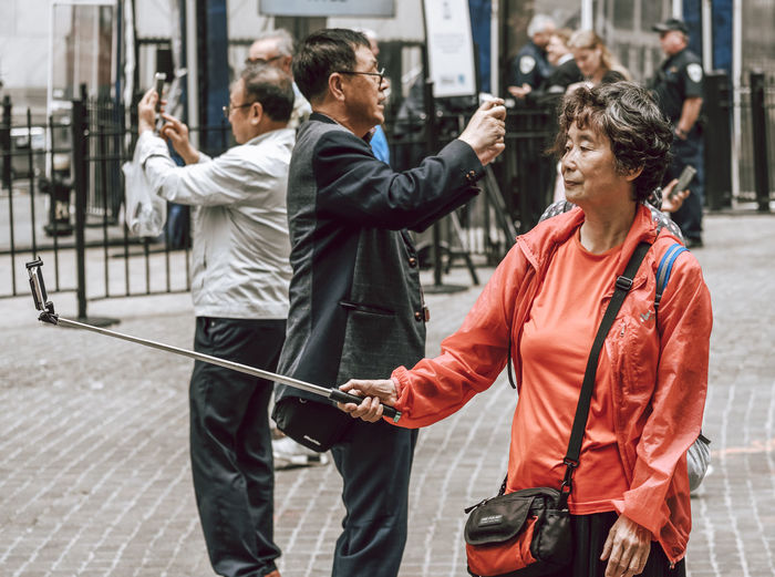 People photographing with mobile phone in city
