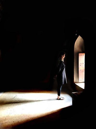 Rear view of girl walking in illuminated corridor