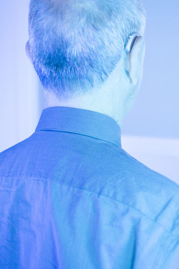 Rear view of man against blue background