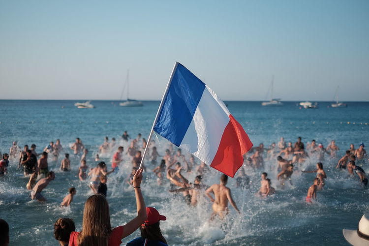 Woman holding french flag with people in sea against clear sky during sunset