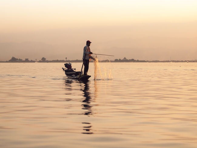 Beauty In Nature Calm Clear Sky Fisherman Holding Inle Inle Lake Men Myanmar Nature Orange Color Outline Rippled Scenics Sea Shan State Silhouette Solitude Standing Sunset Tranquil Scene Tranquility Water Waterfront