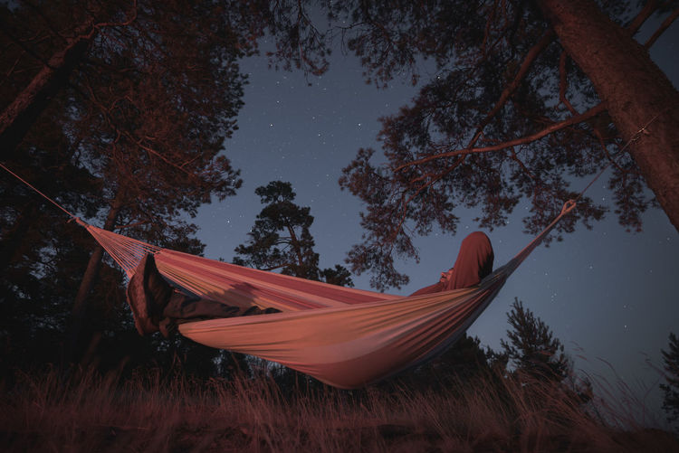 A man sleeps in a hammock on a starry night. campfire lighting. night photography