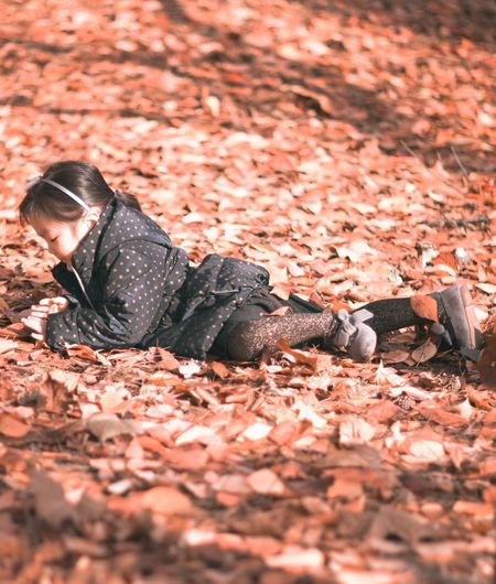 Girl lying on autumn leaves at field