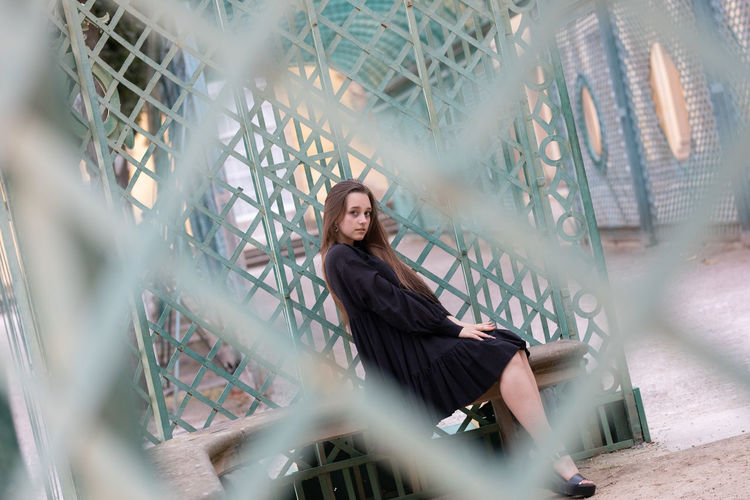 Portrait of young woman looking through fence