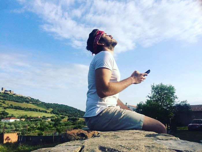 Side view of man holding mobile phone while relaxing on rock against sky