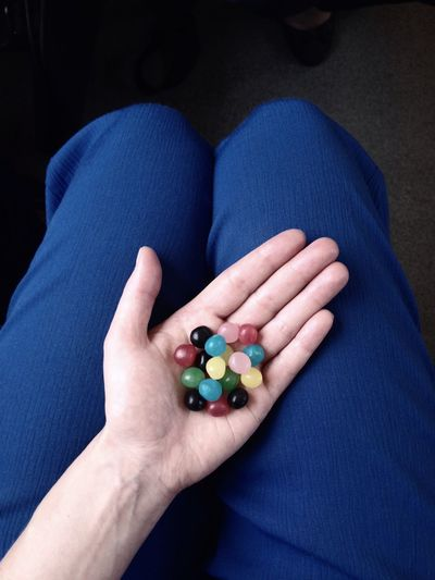 Midsection of woman holding colorful marbles