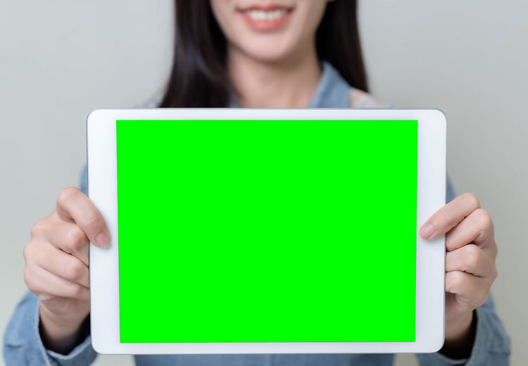 Midsection of woman holding smart phone against white background