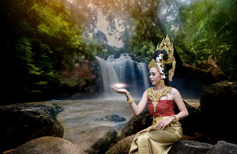 Beautiful young woman wearing crown and traditional clothing while sitting against waterfall in forest