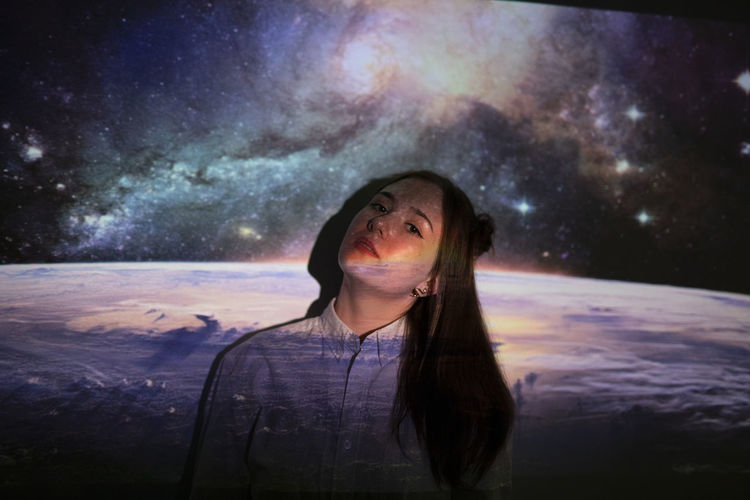 Portrait of woman against sky at night