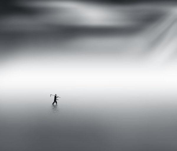 Silhouette man walking in river water under mist at dawn