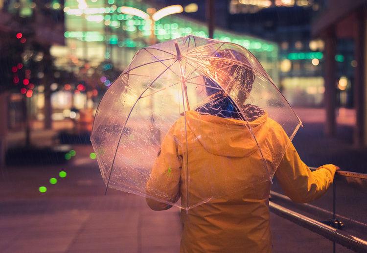 Man holding umbrella while standing on street during rainy season