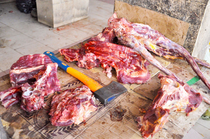 High angle view of beef with axe at butcher shop