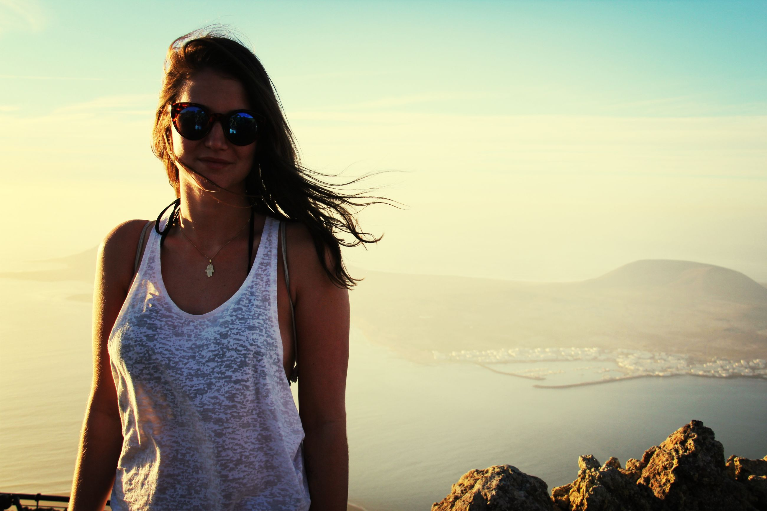 young adult, person, portrait, looking at camera, lifestyles, sunglasses, young women, casual clothing, leisure activity, mountain, front view, standing, smiling, sky, long hair, three quarter length, sunlight