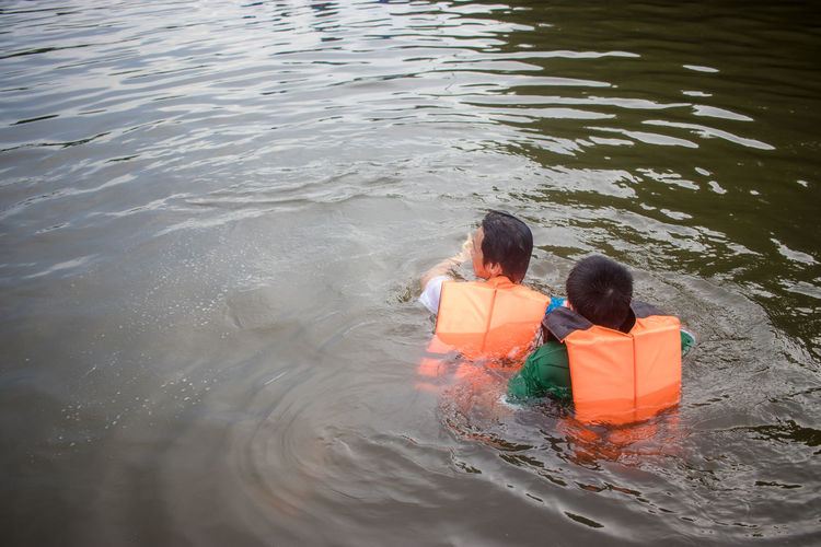 Rear view of man and boy swimming in river with life jacket