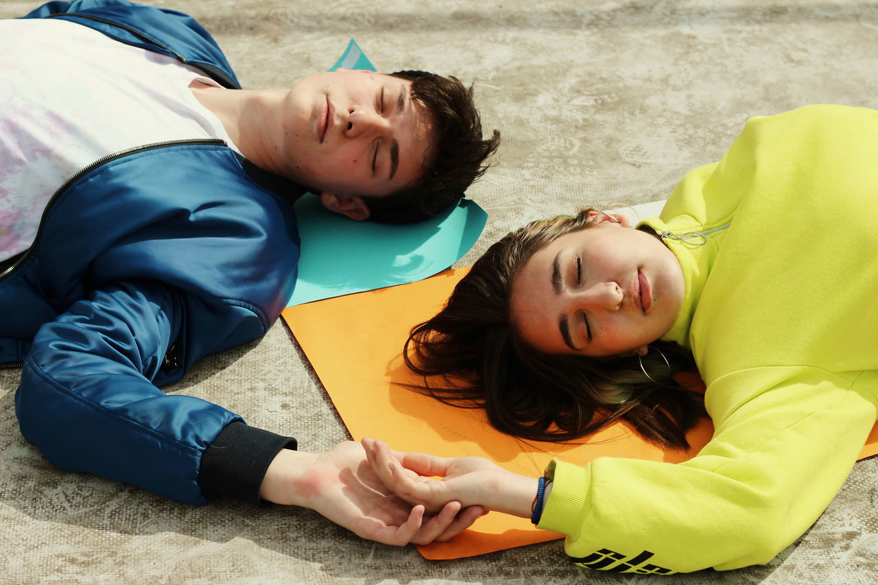 High angle view of friends sleeping on exercise mats