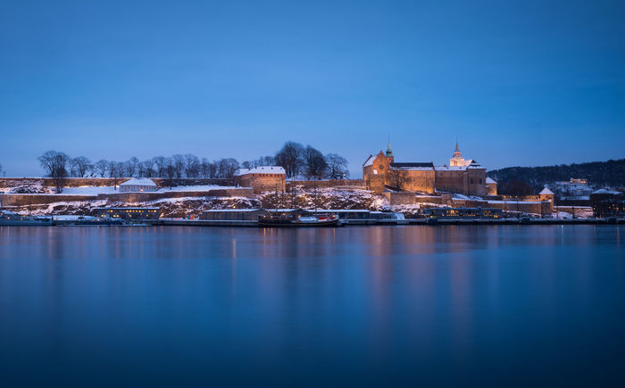 Akershus Fortress in the twilight, winter time. Building Exterior Architecture Water Built Structure Waterfront Blue No People Building Clear Sky Reflection Travel Destinations Outdoors Medieval Architecture Attraction Castle Fortress Europe Oslo Norway Harbour Scenic Seascape Sea Old Town Old EyeEmNewHere
