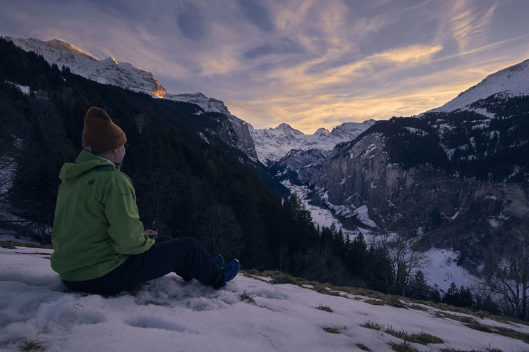 Mature man sitting on snowcapped mountain against sky during sunset