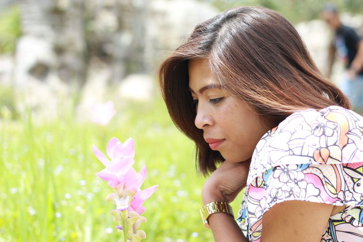 Side View Of Woman Looking At Purple Flowers Blooming Outdoors