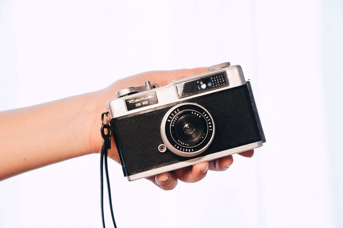 Photography Themes Camera - Photographic Equipment Human Hand White Background Photographing Holding One Person Human Body Part Photographer Technology Studio Shot Leisure Activity Old-fashioned Camera Real People Digital Camera Retro Styled Lifestyles SLR Camera Close-up EyeEmNewHere