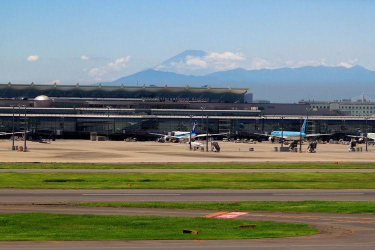 Airplanes at narita international airport against sky
