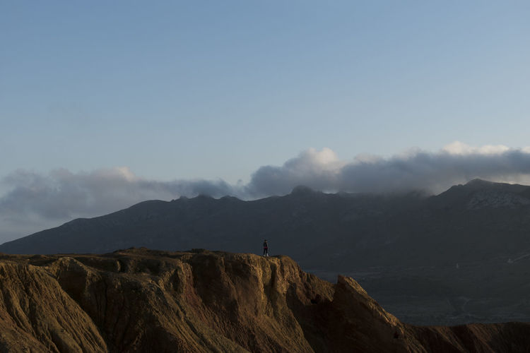 Woman on old abandoned mine view the mountains with clouds background in murcia, spain