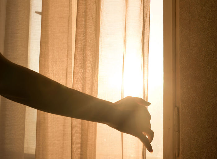 Female arm reaching out to open a curtain - warm sun light shining through Opening Curtains Window Warm Tender Reaching Out Reaching Opening One Person Mysterious Looking Into The Sun Light And Shadow Lens Flare Interior Indoors  Human Hand Human Body Part Home Interior Drapes  Curtain Concept Arm Sunlight Silhouette EyeEmNewHere EyeEmNewHere