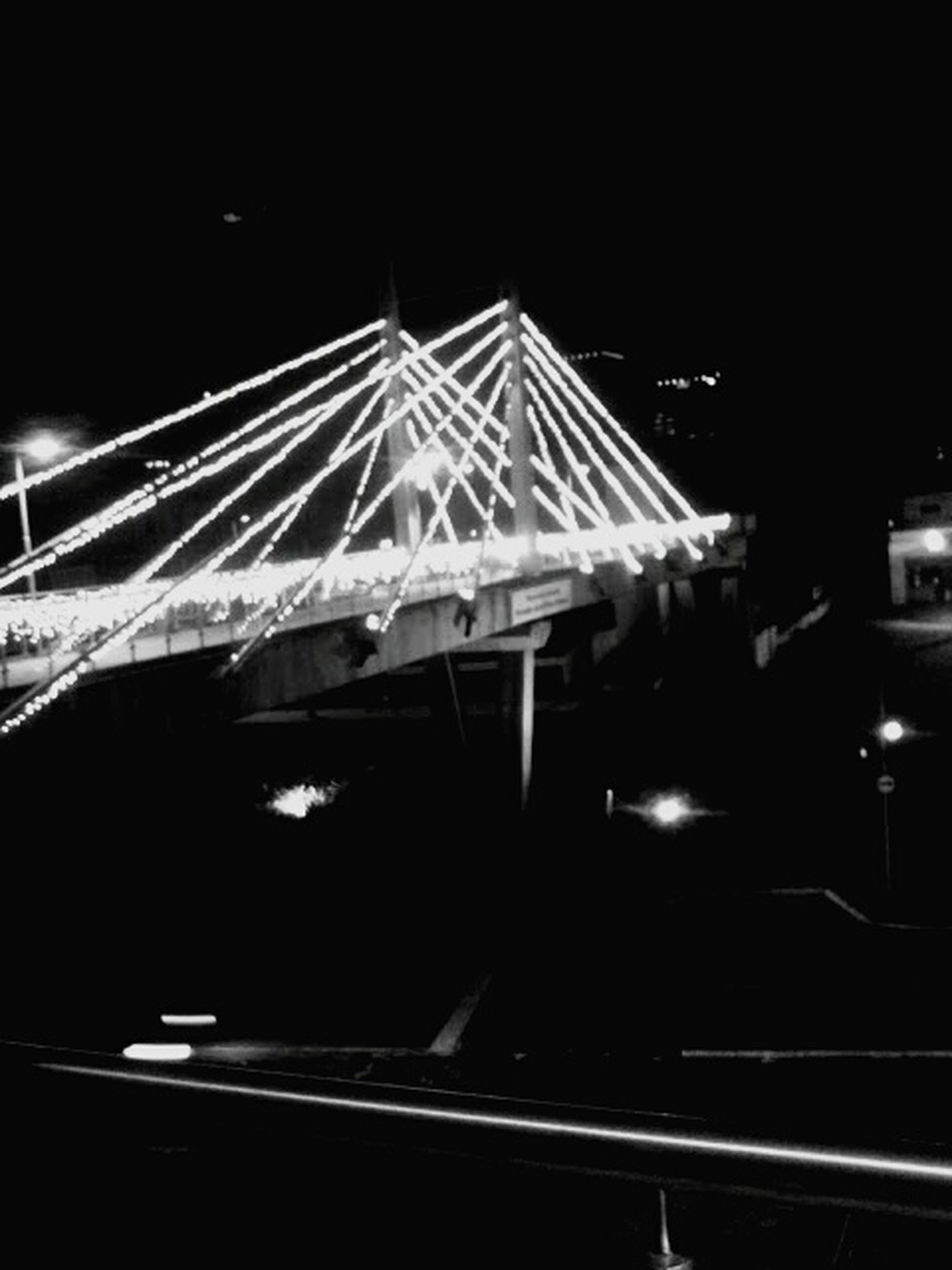 night, illuminated, low angle view, built structure, architecture, connection, metal, transportation, bridge - man made structure, no people, engineering, lighting equipment, railing, outdoors, clear sky, dark, electricity, sky, metallic, light - natural phenomenon