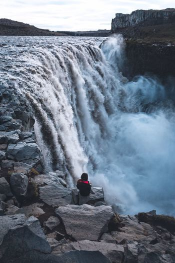 High Angle View Of Woman Sitting On Rock By Waterfall