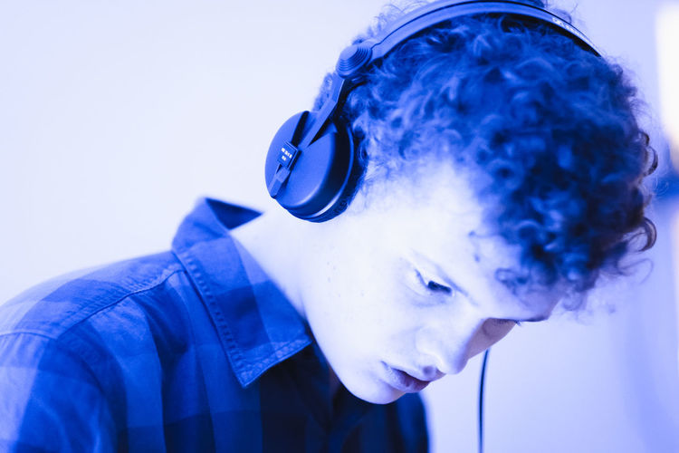 Close-up of young man listening music