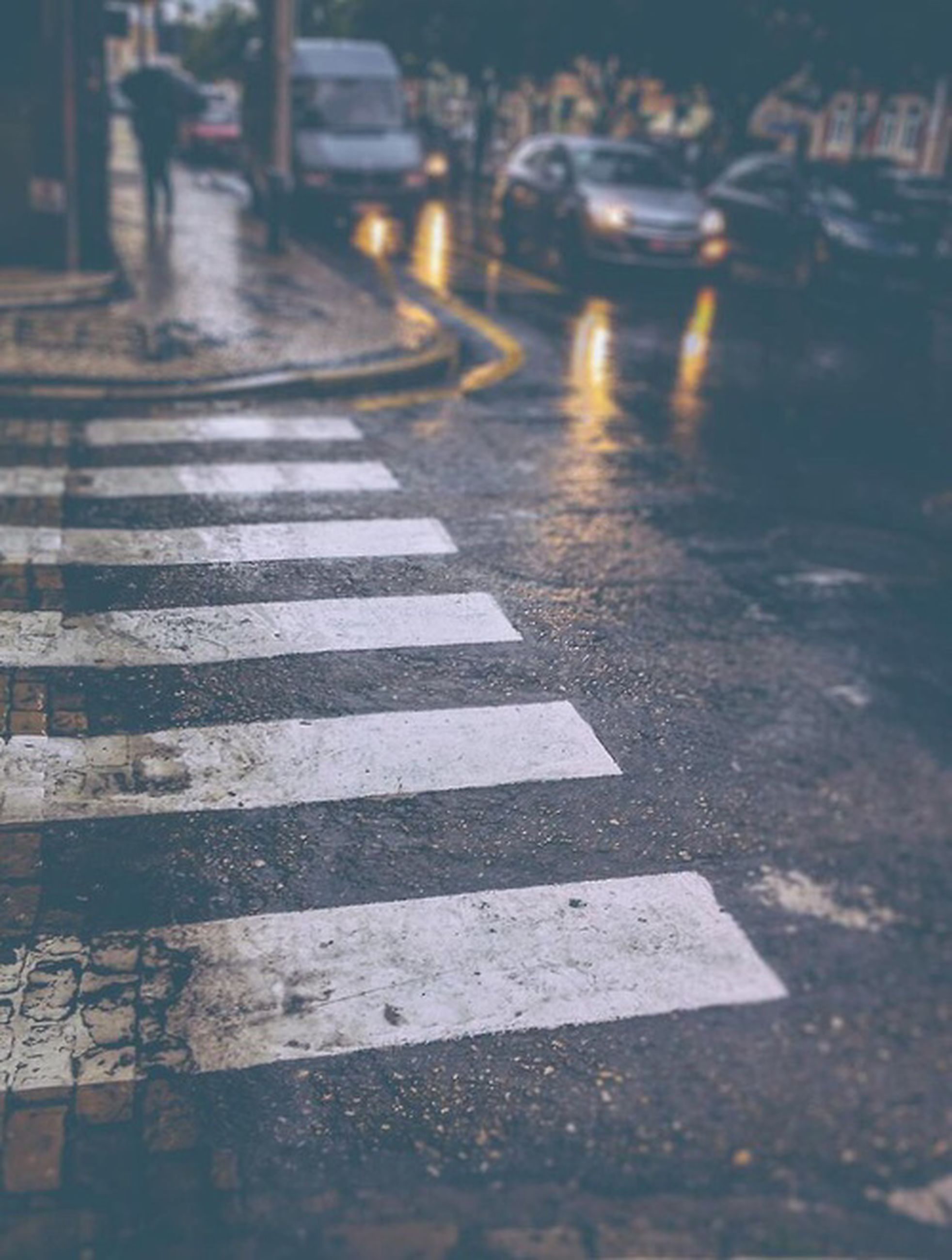 street, road marking, transportation, road, zebra crossing, asphalt, city, car, the way forward, city street, sidewalk, high angle view, sunlight, shadow, incidental people, outdoors, building exterior, city life, land vehicle, day
