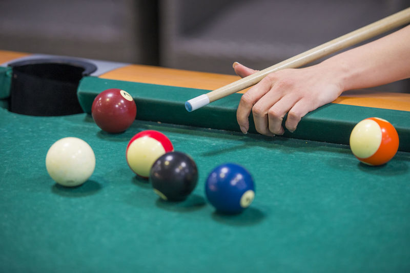 Cropped hand of woman playing pool