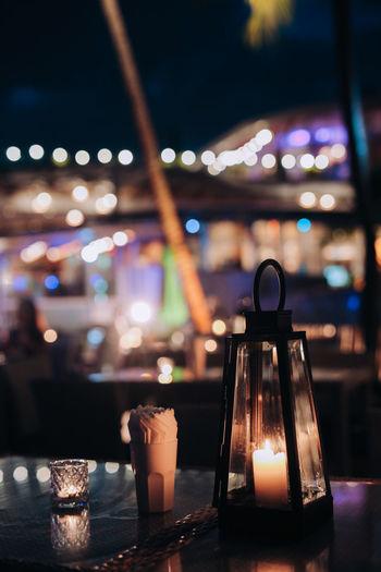 Close-up of illuminated lamp on table at night