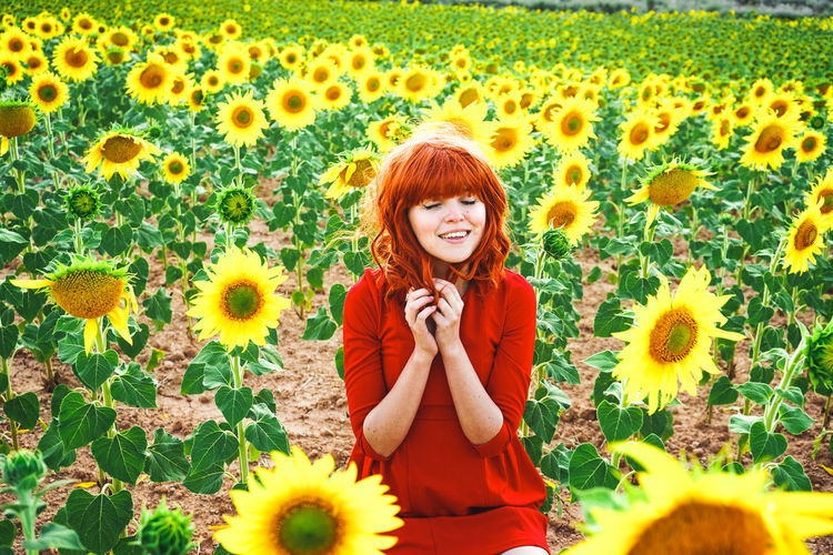 Portrait of smiling woman standing on sunflower field