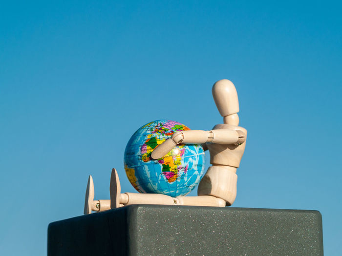 Low angle view of wooden figurine with globe against clear blue sky
