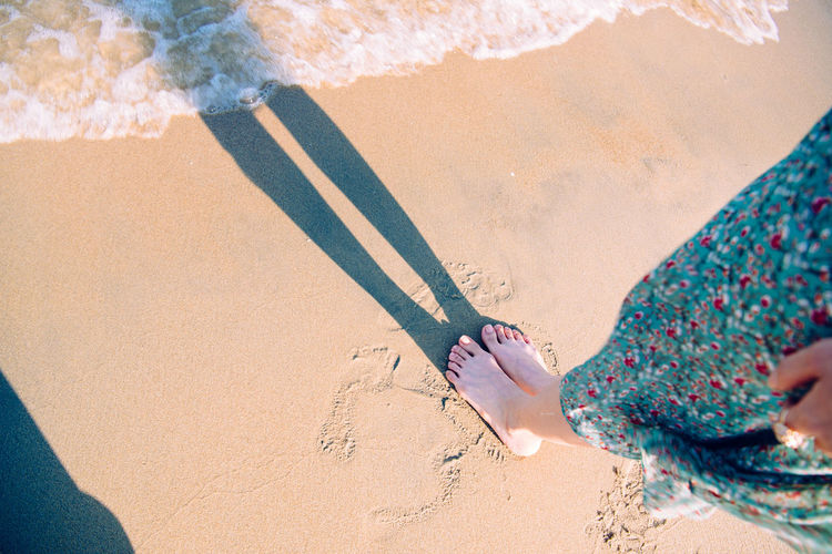 Low section of woman standing on sand at beach