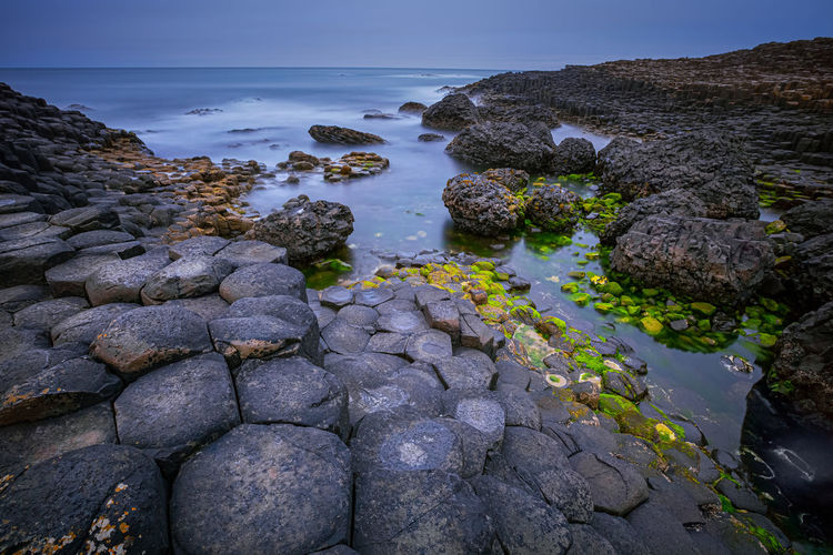 High angle view of rocks by sea against sky