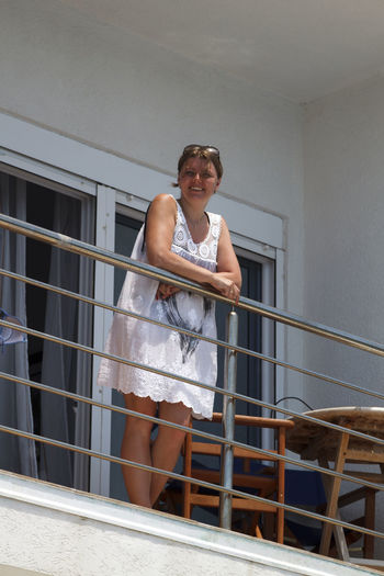 Low angle portrait of smiling woman standing by railing in balcony