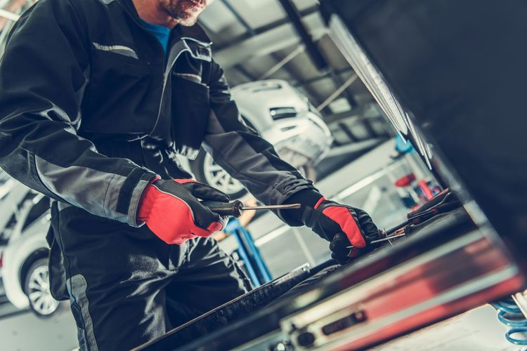 Midsection of man repairing car in garage
