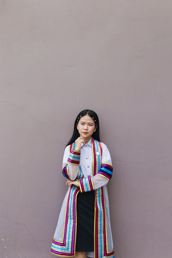 Young woman in traditional clothing standing against wall