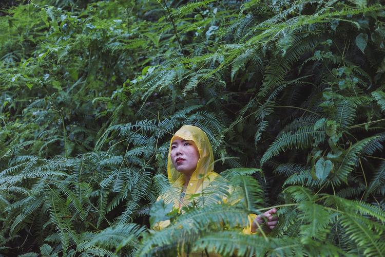Woman in raincoat standing against plants