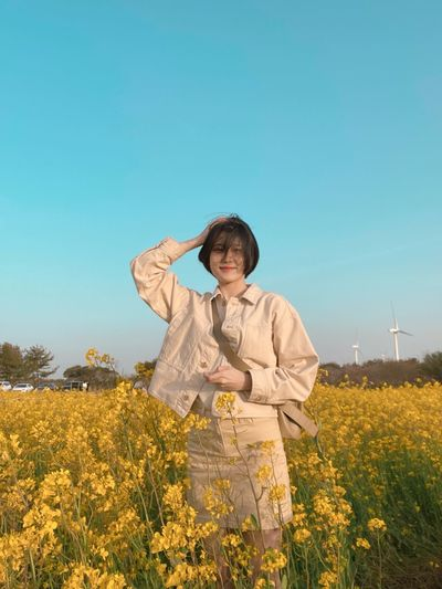 Full length of woman standing on field against clear sky